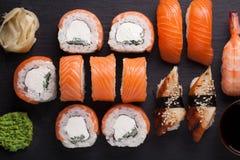 与三文鱼、虾、鳗鱼和寿司卷费城的特写镜头寿司集合生鱼片在石板岩服务 顶视图 库存图片