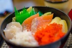 与三文鱼、金枪鱼和乌贼的新鲜的未加工海鲜在米 免版税图库摄影