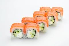 与三文鱼、鲕梨、费城和黄瓜的寿司卷在白色背景 免版税图库摄影