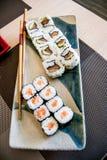 与三文鱼、鲕梨和金枪鱼的寿司在有筷子的一块板材 免版税图库摄影