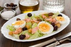 与三文鱼、鸡蛋和橄榄的沙拉在白色盘 库存图片