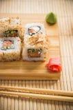 与三文鱼、黄瓜和金枪鱼皮肤的寿司卷在一个木板 免版税库存照片