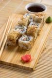 与三文鱼、黄瓜和金枪鱼皮肤的寿司卷在一个木板 库存图片