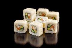 与三文鱼、黄瓜和鲕梨的开胃寿司卷在黑背景 图库摄影