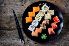 与三文鱼、tobiko鱼子酱、煎蛋卷、黄瓜、芝麻和软干酪的自创寿司在老木背景 土气样式 免版税库存照片