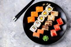 与三文鱼、tobiko鱼子酱、煎蛋卷、黄瓜、芝麻和软干酪的自创寿司在老木背景 土气样式 库存图片