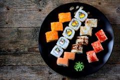 与三文鱼、tobiko鱼子酱、煎蛋卷、黄瓜、芝麻和软干酪的自创寿司在老木背景 土气样式 库存照片