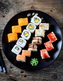 与三文鱼、tobiko鱼子酱、煎蛋卷、黄瓜、芝麻和软干酪的自创寿司在老木背景 土气样式 免版税图库摄影