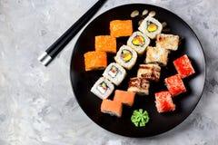 与三文鱼、tobiko鱼子酱、煎蛋卷、黄瓜、芝麻和软干酪的自创寿司在老木背景 土气样式 免版税库存图片
