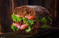 与三文鱼和柠檬的自创三明治在黑暗的木背景 选择聚焦 野餐概念 免版税图库摄影