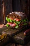 与三文鱼和柠檬的自创三明治在黑暗的木背景 选择聚焦 野餐概念 免版税库存照片