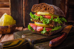与三文鱼和柠檬的自创三明治在黑暗的木背景 选择聚焦 野餐概念 库存图片