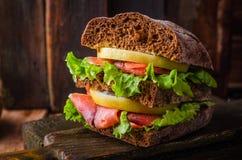 与三文鱼和柠檬的自创三明治在黑暗的木背景 选择聚焦 野餐概念 库存照片