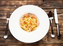 与三文鱼和鱼子酱的面团意大利细面条在向求爱的一个白色盘 库存照片