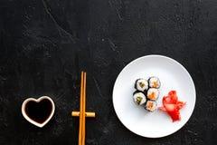 与三文鱼和鲕梨的寿司卷在板材用酱油,筷子,在黑背景顶视图copyspace的山葵 免版税库存照片