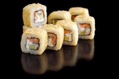 与三文鱼和鲕梨的被烘烤的寿司卷在一个黑背景特写镜头 库存照片