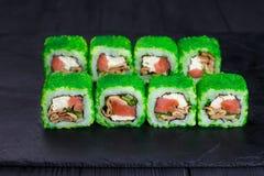 与三文鱼和鳗鱼的鲜美开胃uramaki寿司卷,被盖 图库摄影