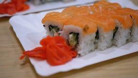 与三文鱼的寿司劳斯在一块白色板材在日本料理店 股票视频