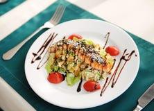 与三文鱼的沙拉在一块白色板材 服务在与一张绿色桌布的一张桌上在餐馆 免版税库存图片