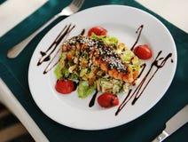与三文鱼的沙拉在一块白色板材 服务在与一张绿色桌布的一张桌上在餐馆 库存照片