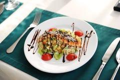 与三文鱼的沙拉在一块白色板材 服务在与一张绿色桌布的一张桌上在餐馆 图库摄影