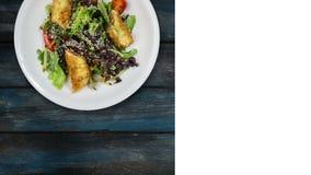 与三文鱼的沙拉在面包渣用莴苣和芝麻籽 在木背景转动 社会的方形的布局 股票录像