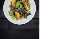 与三文鱼的沙拉在面包渣用莴苣和芝麻籽 在黑木背景转动 方形的布局为 股票视频