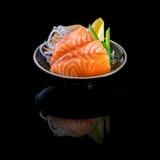 与三文鱼的生鱼片在一个黑色的盘子 在黑背景与 库存照片