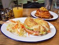 与三文鱼的百吉卷用薄煎饼和橙汁在背景 库存照片
