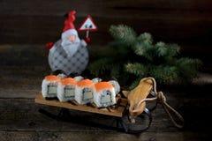 与三文鱼的自创寿司在小雪橇,圣诞节背景 免版税库存图片