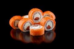 与三文鱼金枪鱼和费城乳酪的被提炼的寿司卷在一个黑背景特写镜头 库存图片