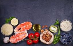 与三文鱼鱼、蔬菜、水果和成份的戒毒所健康食物概念烹调的 库存照片
