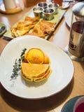 与三文鱼鱼和茶壶的薄煎饼在咖啡馆的桌上 鲜美食物 库存图片