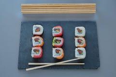 与三文鱼,大虾,鲕梨,奶油奶酪的卷寿司 寿司菜单 免版税图库摄影