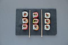 与三文鱼,大虾,鲕梨,奶油奶酪的卷寿司 寿司菜单 图库摄影