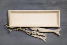 与三条手工制造鱼的白色木制框架海装饰的 图库摄影