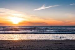 与三脚架射击日落的照相机在与美好的日落的海滩 库存图片
