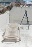 与三脚架的大厦大阳台和在帕罗斯岛,希腊的一张躺椅 库存图片