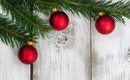 与三件红色装饰品的盛大冷杉分支在土气白色木 库存照片