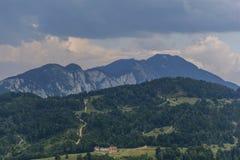 与上升房子和乡下公路的美丽如画的农村风景在喀尔巴阡山脉,罗马尼亚 库存照片