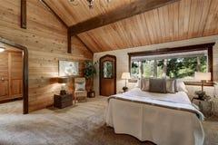 与上流放光的天花板的木卧室内部 图库摄影
