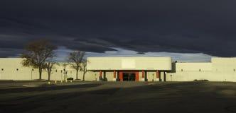 与上面不祥的云彩的空的零售店 免版税库存照片