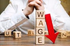 与下来词薪水和红色箭头的木块 薪金减少 在赢利的下落 危机绘制下降的财务费率 降职 低赢利 免版税库存图片