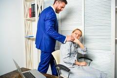 与下级雇员的上司不能接受的行为 上司女性办公室同事接触肩膀  疲乏的女工 免版税图库摄影