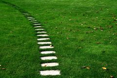 与下落的叶子的石秋天路横跨耕种的草坪 免版税库存图片