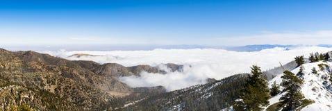 与下落的雪和白色云彩海的晴朗的冬日在足迹的对Mt圣安东尼奥(Mt鲍尔迪),洛杉矶县, 图库摄影