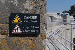 与下跌从峭壁边缘的人的标志的危险突然的下落标志黄色警告的三角和保留孩子在控制标志下 免版税库存照片