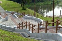 与下降山的扶手栏杆的具体楼梯到河在低地 免版税图库摄影