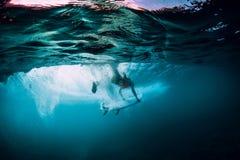 与下面桶波浪的有吸引力的冲浪者妇女下潜水中 免版税图库摄影