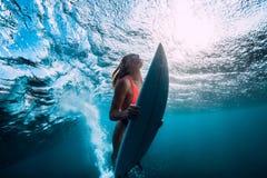 与下面海浪的有吸引力的冲浪者妇女下潜水中 免版税库存图片